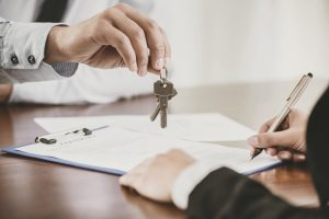 A man hands keys over to client signing a lease
