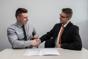 2 businessmen at a table shaking hands