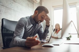 Man struggles with occupational stress while working at computer