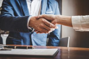 Commercial Real estate agent and customers shaking hands together celebrating finished contract after about home insurance and investment loan, handshake and successful deal
