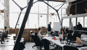 A team sitting at the tables with computers and laptops and listening to the colleague standing by the flipchart in a spacious light modern office
