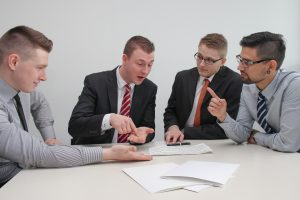 4 young professionals discussing business at a meeting table
