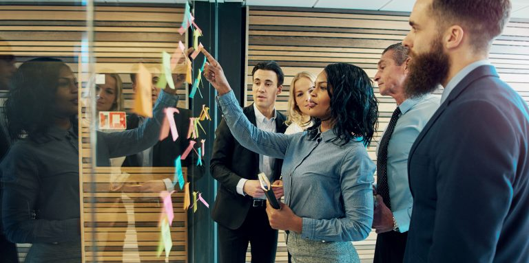 Creative group of business people brainstorming putting sticky notes on glass wall in office