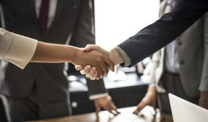 Commercial Real estate agent and customers shaking hands together celebrating finished contract