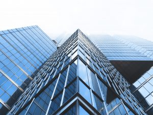 A steep ground level view of a tall building with large glass windows