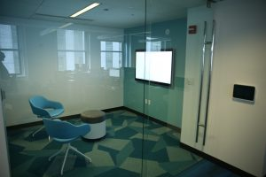 A small meeting room separated by a glass wall and glass door within an office space