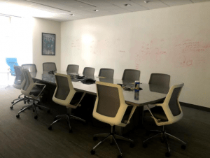 A meeting room with whiteboard walls with partially erased writing