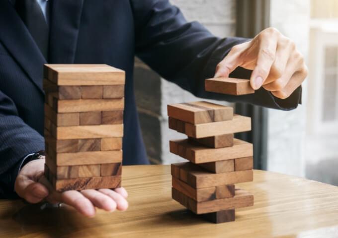 a businessman stacking Jenga blocks