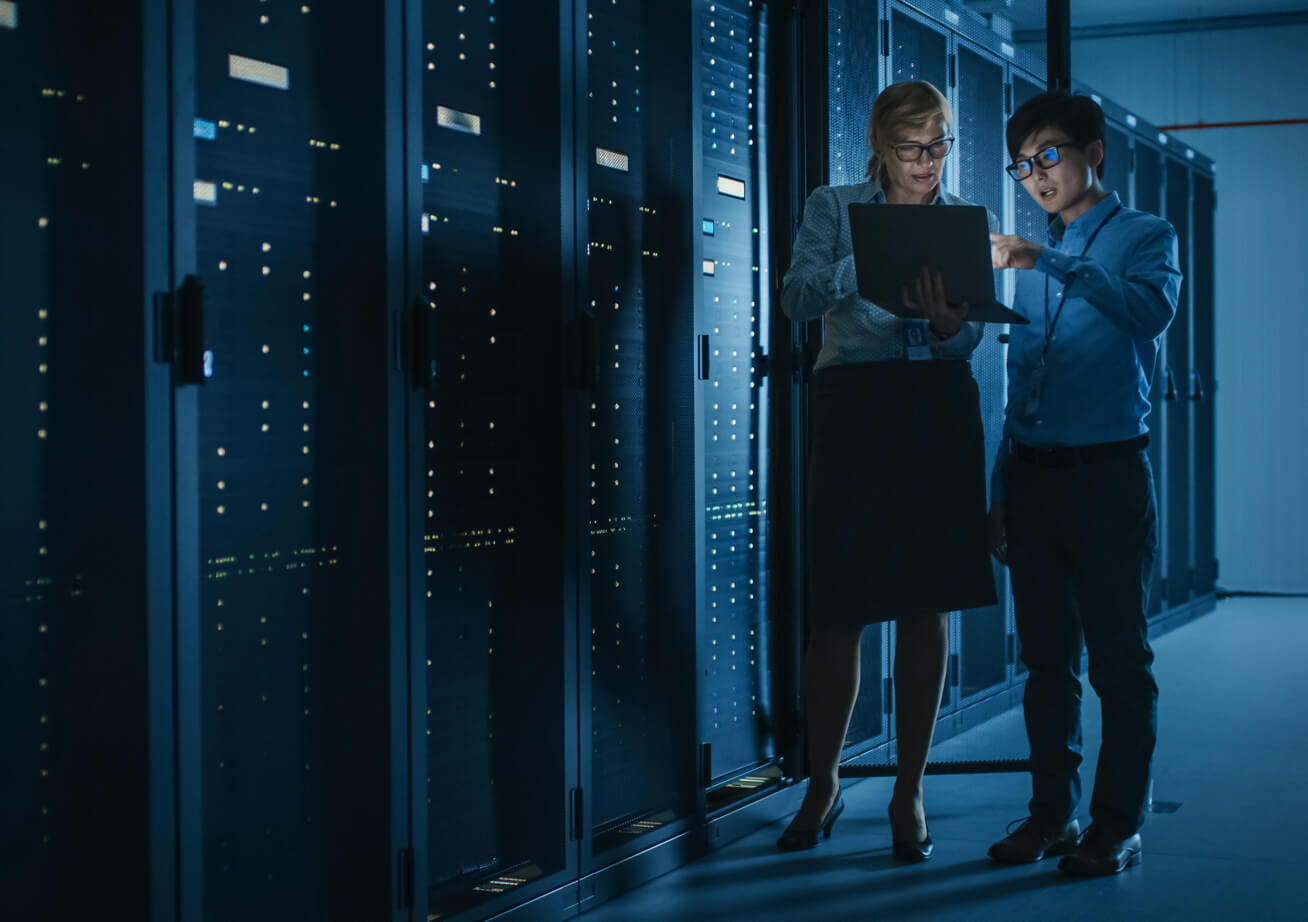 Two employees discussing work in the dark interior of a server room