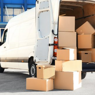 A large number of cardboard boxes stacked inside and outside of a moving van