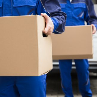 Two men in blue work suits carrying cardboard boxes