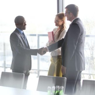 A realtor and client shake hands in a meeting room after a discussion