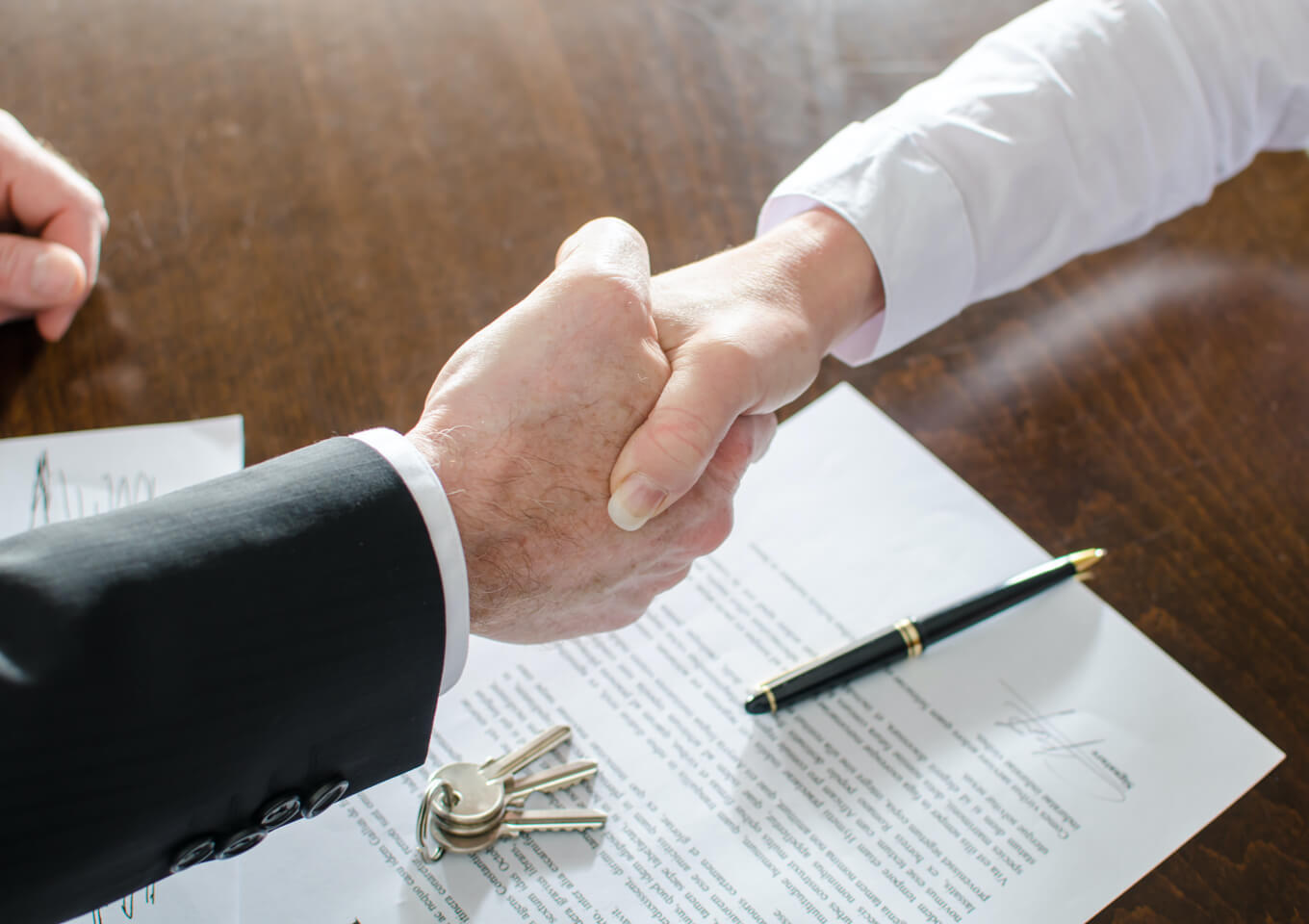 Two people shake hands after signing a lease