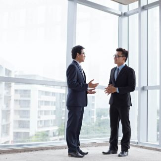 Two men discuss a business sale near the glass wall window of an office corner