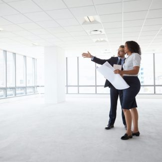 A business man and realtor plan out office space in an empty building space